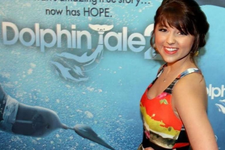 Caroline Kole standing in front of Dolphin Tale poster