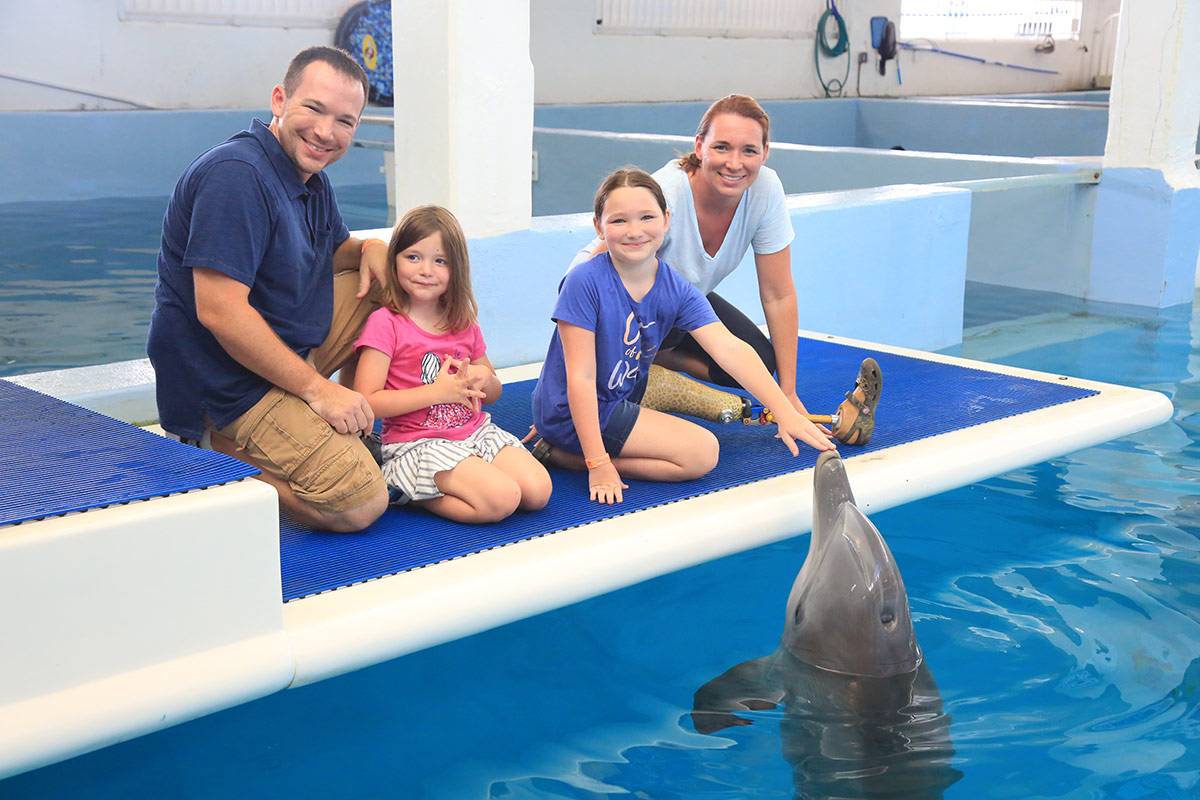 Leya Allen leg amputee meets Winter and Hope dolphins