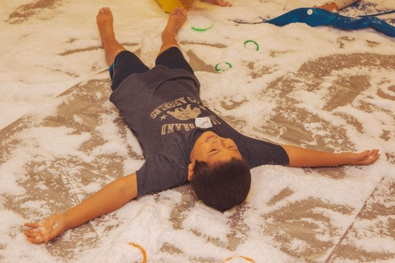Holiday Hoopla Camper making a snow angel on the floor